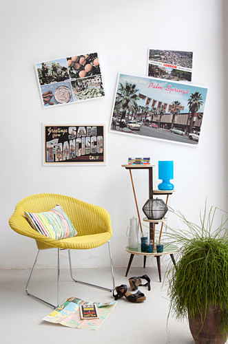 Huge postcards on wall above yellow easy chair and etagere