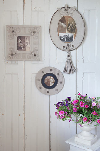 Urn of petunias below picture frames made from corrugated cardboard