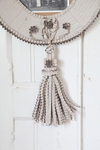 Detail eines Bilderrahmen aus Wellpappe mit einer Troddel