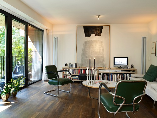 Exotic-wood parquet floor, modern artwork and glass wall leading to balcony in retro living room
