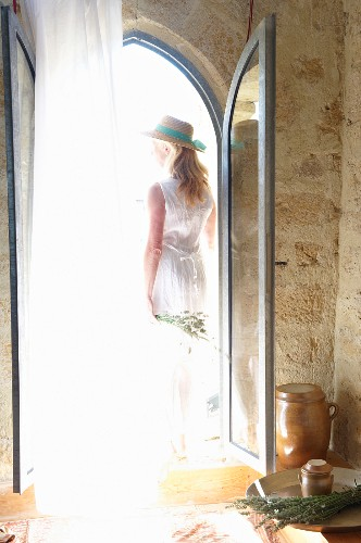 View of blonde woman standing outside open glass door