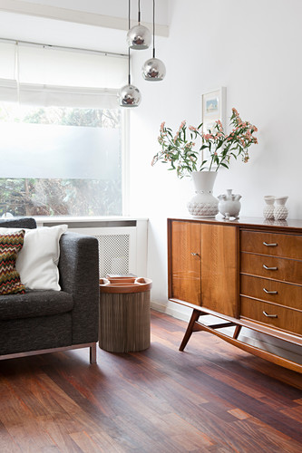 Retro sideboard next to modern grey sofa in living room