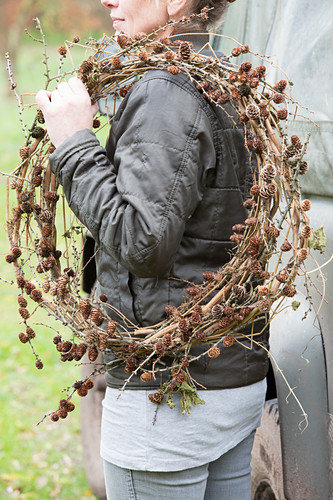 Woman carrying larch branches with cones