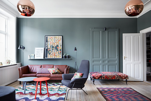 Eclectic furnishings and petrol-blue walls in living room with panelled doors