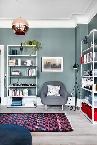 Simple shelves against petrol-blue walls in living room