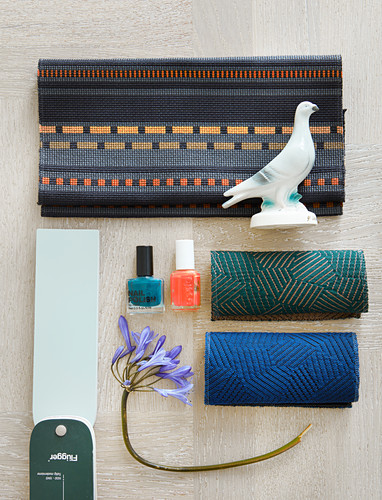 Mood board with fabric swatches, nail polishes, flower and bird figurine
