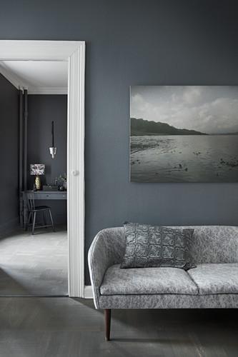 Retro sofa below gloomy landscape photograph on grey wall