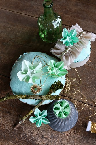 Arrangement of ornaments and green origami flowers