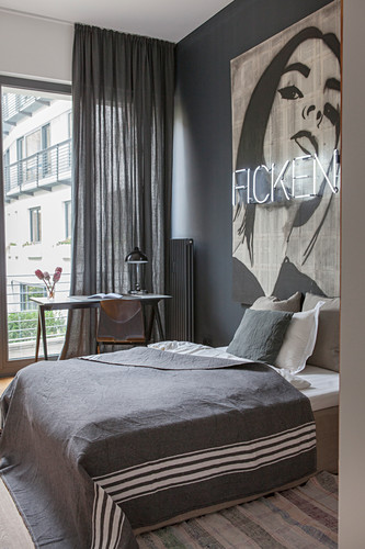 Bedroom in shades of grey with large artwork and neon lettering