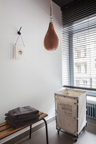Punchball suspended above laundry basket and bench in bathroom