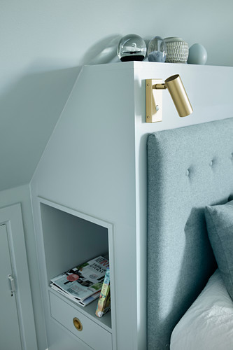 Niche and drawer in bed headboard below sloping ceiling
