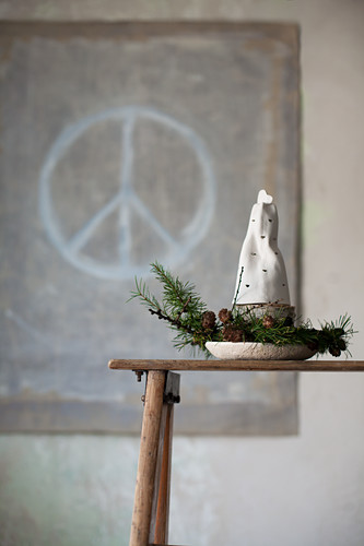Pottery bell and larch twigs in front of peace symbol