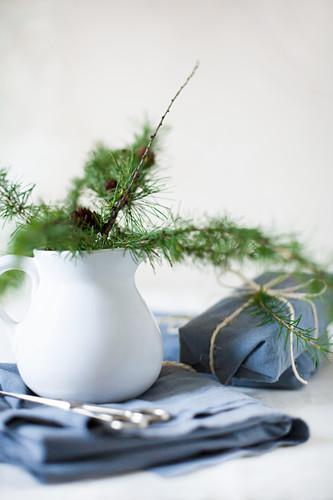 Lärchenzweige im weißen Krug und in blauen Stoff verpackte Geschenke