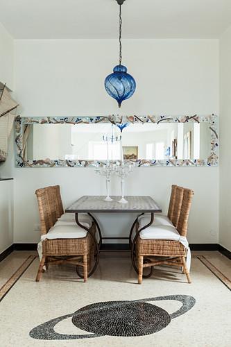 Mosaic of Saturn on floor in front of Mediterranean dining set below long mirror on wall