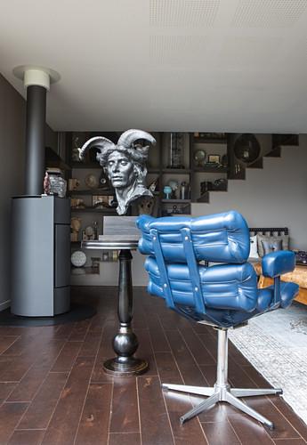 Büste auf dem Beistelltisch neben blauem Ledersessel im Wohnzimmer