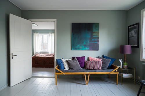 Various scatter cushions on old wooden couch with colour scheme matching painting on wall above