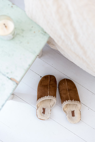 Sheepskin and leather slippers next to bed
