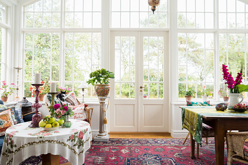 Tables, seating and potted plants in conservatory