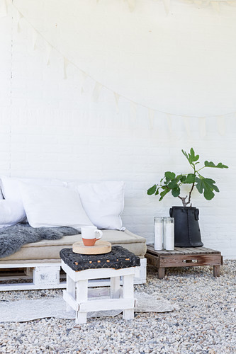 Furniture made from pallets on terrace with white wall