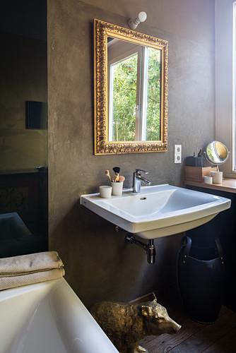 Sink below gilt-framed mirror on bathroom wall