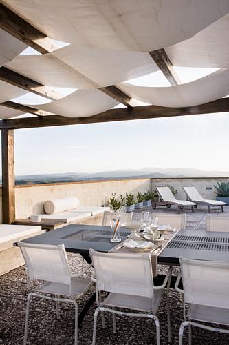 Tisch mit Gedeck für Zwei auf der Terrasse, im Hintergründ Liegen