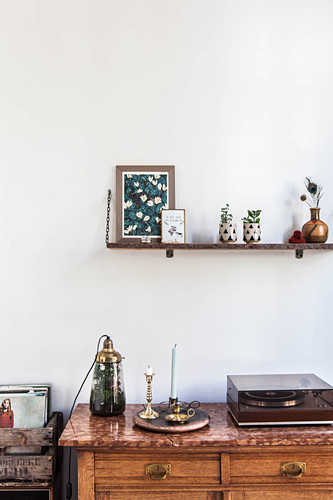 Ornaments on wall-mounted shelf above record player on sideboard