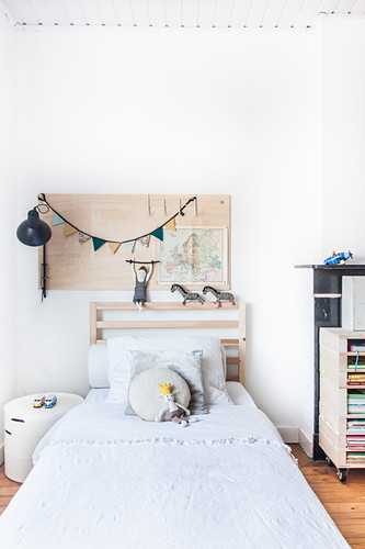 Pinboard on white wall above bed in child's bedroom
