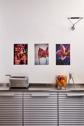 Pictures above kitchen counter with corrugated fronts, toaster and fruit basket