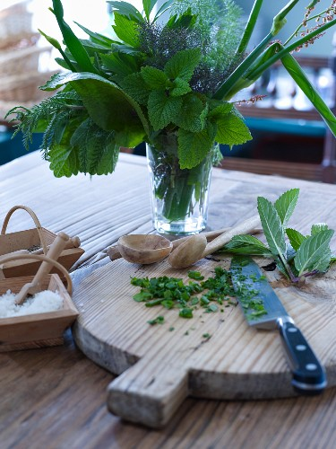 Various herbs in glass of water next to chopping board