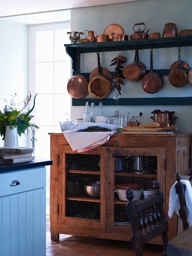 Copper pans on shelves above open-fronted wooden cabinet