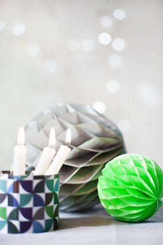 Honeycomb paper balls and candles in glass holder
