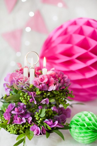 Flower arrangement with candles on cake stand and colourful honeycomb paper balls