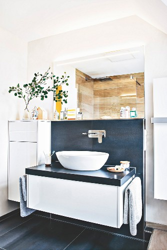 A white, top-mounted basin in front of dark wall tiles