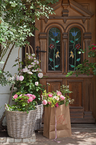 Bouquet of lady's mantle and roses in paper bag and baskets outside front door