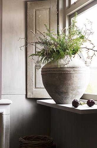 Wintry bouquet of twigs in stone pot on windowsill