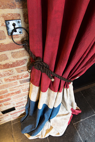 Gathered Union-flag-patterned curtains against brick wall