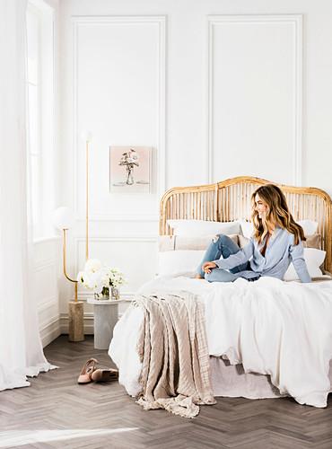 Junge Frau auf Doppelbett vor weißer Kassettenverkleidung im Schlafzimmer