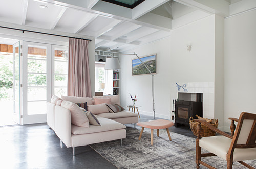 Pale corner sofa in front of fireplace in open-plan interior with terrace doors