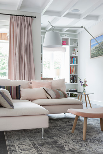 Scatter cushions on pale corner sofa in open-plan interior