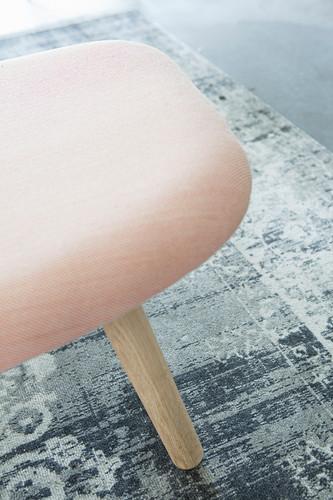 Pink upholstered stool on grey rug