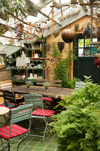 Blick in alte Gärtnerei mit Gartentisch und Gartenstühlen