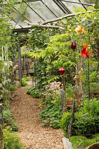 Mulched path leading through plants and decorative garden stakes in green house of old nursery