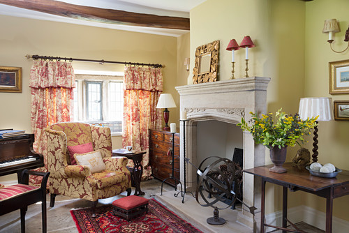 Armchair and grand piano in front of fireplace in rustic living room