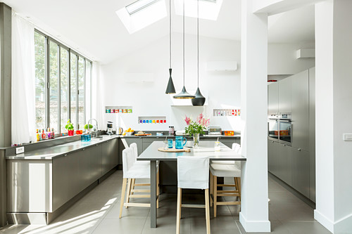 Elegant grey and white kitchen with glass wall and dining area