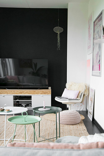 Various side tables in living room with black accent wall