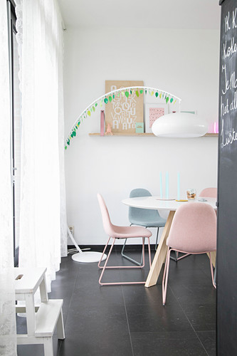 Arc lamp over dining table with upholstered chairs in pastel shades
