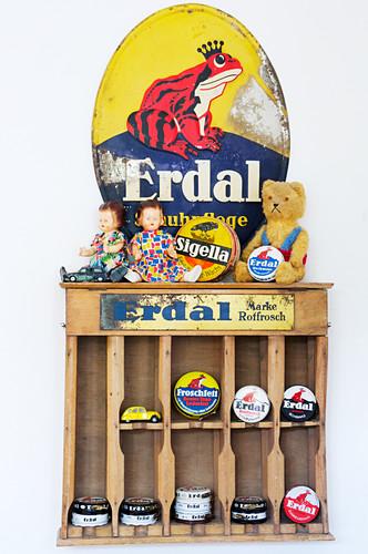 Enamel sign above old wooden shelves of dolls and shoe-polish tins