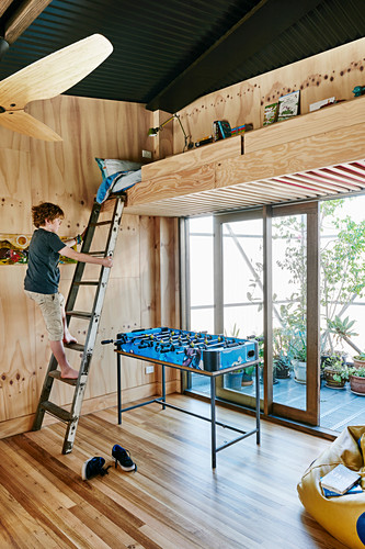 Hochbett aus Holz, Junge auf der Leiter, darunter Kickertisch vor Balkontür