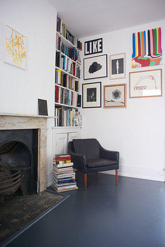 Armchair in corner below bookcase and gallery of pictures on wall