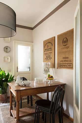Pictures made from hessian sacks above old wooden table and stacked chairs